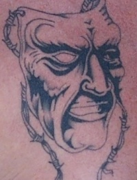 Ugly mask on barb wire tattoo